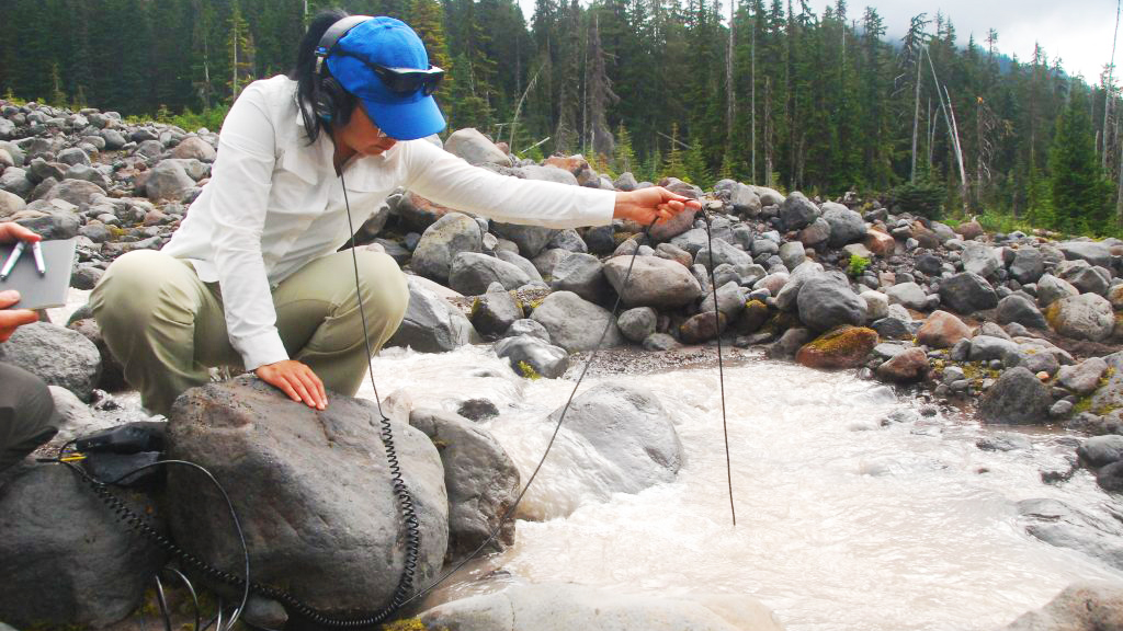 A landscape of lose rocks, through which a small stream flows. Pine trees are visible in the background. A person is crouched on a rock, wearing headphones and lowering a hydrophone on a cable into the running stream. They are wearing green trousers, a white shirt and a blue baseball cap.
